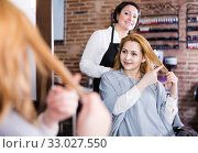Купить «Young woman points necessary length of hair», фото № 33027550, снято 7 марта 2017 г. (c) Яков Филимонов / Фотобанк Лори