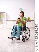 Купить «Young male invalid in wheel-chair suffering at home», фото № 33028510, снято 23 июля 2019 г. (c) Elnur / Фотобанк Лори