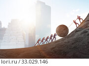 Teamwork example with business people pushing stone to top. Стоковое фото, фотограф Elnur / Фотобанк Лори
