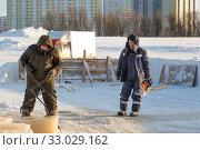 Fitter with steel tongs pulls out ice block. Стоковое фото, фотограф Андрей Кузнецов / Фотобанк Лори