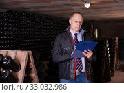 Winemaker with clipboard in wine cellar. Стоковое фото, фотограф Яков Филимонов / Фотобанк Лори