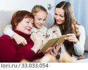 Купить «Grandmother with daughter and granddaughter reading», фото № 33033054, снято 25 ноября 2017 г. (c) Яков Филимонов / Фотобанк Лори