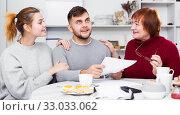 Купить «Cheerful family with papers», фото № 33033062, снято 27 ноября 2017 г. (c) Яков Филимонов / Фотобанк Лори