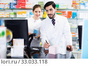 Two pharmacists are attentively stocktaking medicines with computer and note on paper. Стоковое фото, фотограф Яков Филимонов / Фотобанк Лори
