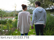 Купить «Young couple holding hands in the garden», фото № 33033718, снято 28 ноября 2019 г. (c) Wavebreak Media / Фотобанк Лори