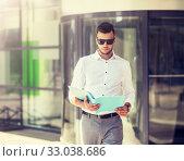 Купить «young man with business file on city street», фото № 33038686, снято 21 августа 2016 г. (c) Syda Productions / Фотобанк Лори