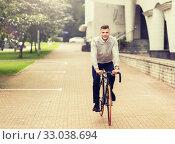 Купить «young man riding bicycle on city street», фото № 33038694, снято 21 августа 2016 г. (c) Syda Productions / Фотобанк Лори