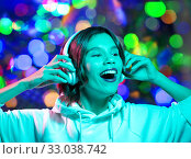 Купить «woman in headphones listening to music over lights», фото № 33038742, снято 30 сентября 2019 г. (c) Syda Productions / Фотобанк Лори