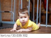 Caucasian baby in yellow bodysuit lying on floor and looking at camera. Стоковое фото, фотограф Кекяляйнен Андрей / Фотобанк Лори