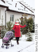 Купить «Fashionable stylish young mother stands with her baby stroller in courtyard at winter. Showing street covered with snow», фото № 33039126, снято 4 января 2020 г. (c) Кекяляйнен Андрей / Фотобанк Лори
