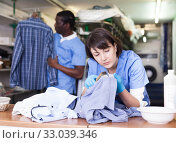 Купить «Female laundry worker during daily work», фото № 33039346, снято 15 января 2019 г. (c) Яков Филимонов / Фотобанк Лори