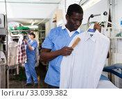 Купить «Laundry worker during daily work», фото № 33039382, снято 15 января 2019 г. (c) Яков Филимонов / Фотобанк Лори
