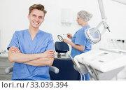 Купить «Male dentist in dental office with hands crossed», фото № 33039394, снято 30 апреля 2019 г. (c) Яков Филимонов / Фотобанк Лори