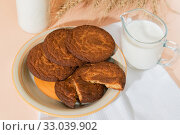 Купить «Healthy food, breakfast, cereal snack. Fresh milk in a glass jug and oatmeal cookies on the table, an armful of ears of corn on a peach color background. A balanced diet, protein and carbohydrates», фото № 33039902, снято 30 ноября 2019 г. (c) Светлана Евграфова / Фотобанк Лори