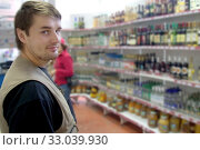 Купить «Russia Samara July 2012: Portrait of a smiling young man on the background of shelves with alcoholic drinks.», фото № 33039930, снято 25 августа 2012 г. (c) Акиньшин Владимир / Фотобанк Лори
