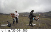 Купить «Two creative artists painting on canvas an easel mountain landscape», видеоролик № 33044586, снято 30 августа 2019 г. (c) А. А. Пирагис / Фотобанк Лори