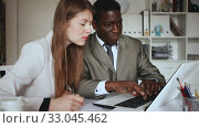 Купить «Young woman and man colleagues working with laptop and papers in office», видеоролик № 33045462, снято 26 апреля 2019 г. (c) Яков Филимонов / Фотобанк Лори