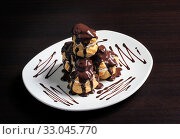 French profiterole with chocolate icing on a plate. Стоковое фото, фотограф Алексей Хромушин / Фотобанк Лори