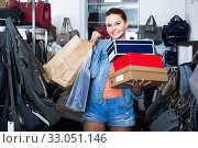 Купить «portrait of teenage girl standing with bags in store with bags», фото № 33051146, снято 15 сентября 2016 г. (c) Яков Филимонов / Фотобанк Лори