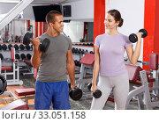 Купить «Couple doing exercises with dumbbells», фото № 33051158, снято 15 октября 2018 г. (c) Яков Филимонов / Фотобанк Лори