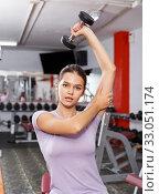 Купить «Woman doing exercises with dumbbells», фото № 33051174, снято 15 октября 2018 г. (c) Яков Филимонов / Фотобанк Лори