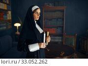 Купить «Young nun in a cassock holds a book and candle», фото № 33052262, снято 14 ноября 2019 г. (c) Tryapitsyn Sergiy / Фотобанк Лори