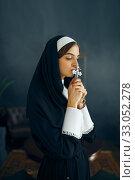 Купить «Young nun in a cassock prays crossed her arms», фото № 33052278, снято 14 ноября 2019 г. (c) Tryapitsyn Sergiy / Фотобанк Лори