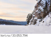 Купить «Winter landscape with a wide frozen river in a snowy wooded valley with high cliffs», фото № 33053794, снято 9 февраля 2020 г. (c) Евгений Харитонов / Фотобанк Лори