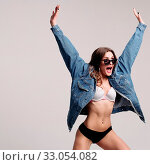 Купить «Crazy young woman in underwear, denim jacket and sunglasses keeping hands up and shouting in studio. Attractive model posing on grey isolated background. Concept of calmness and happiness.», фото № 33054082, снято 31 марта 2020 г. (c) easy Fotostock / Фотобанк Лори