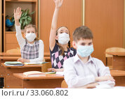 Schoolers wearing protection mask to prevent virus on lesson in classroom. Стоковое фото, фотограф Оксана Кузьмина / Фотобанк Лори