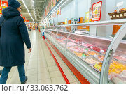 Купить «Russia Samara January 2020: Interior of a grocery store with display cases and freezers. Meat section. Text in Russian: new, fry, soak, bake, discount», фото № 33063762, снято 17 января 2020 г. (c) Акиньшин Владимир / Фотобанк Лори