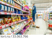 Купить «Russia Samara January 2020: A store employee lays cat food on shelves. Text in Russian: successful purchase, try yummy chicken», фото № 33063766, снято 17 января 2020 г. (c) Акиньшин Владимир / Фотобанк Лори