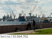 SAINT PETERSBURG, RUSSIA - september 12, 2019: men fishing in view of port on Lieutenant Schmidt embankment on right of Neva river. Редакционное фото, фотограф Короленко Елена / Фотобанк Лори