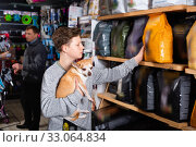 Guy chooses dry food for chihuahua dog in petshop. Стоковое фото, фотограф Яков Филимонов / Фотобанк Лори