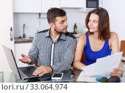 Купить «Smiling young man and woman with financial documents near laptop», фото № 33064974, снято 6 июля 2018 г. (c) Яков Филимонов / Фотобанк Лори