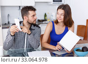 Upset young couple with financial bills and box having conflict. Стоковое фото, фотограф Яков Филимонов / Фотобанк Лори