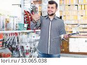 smiling male customer examining various glue guns in store. Стоковое фото, фотограф Яков Филимонов / Фотобанк Лори
