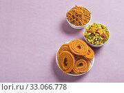 Indian Snack : Chakli, chakali or Murukku and Besan (Gram flour) Sev and chivada or chiwada on pink background. Diwali Food. Стоковое фото, фотограф Dipak Chhagan Shelare / easy Fotostock / Фотобанк Лори