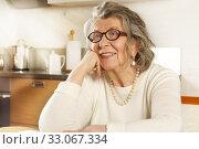 Купить «Portrait of a happy old woman sitting at the kitchen table», фото № 33067334, снято 2 февраля 2020 г. (c) Алексей Кузнецов / Фотобанк Лори