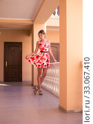 Купить «Beautiful young woman model in summer dress with a full skirt in a red and white flower with a belt», фото № 33067410, снято 25 июля 2016 г. (c) katalinks / Фотобанк Лори