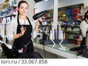 Young woman hairstylist holding blow dryer and hair cutters in cosmetics salon. Стоковое фото, фотограф Яков Филимонов / Фотобанк Лори