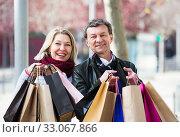 Купить «Couple with shopping bags outdoors», фото № 33067866, снято 17 февраля 2020 г. (c) Яков Филимонов / Фотобанк Лори