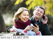 Купить «Couple with mobile phones», фото № 33067870, снято 8 апреля 2020 г. (c) Яков Филимонов / Фотобанк Лори