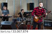 Купить «Guy guitar player and singer practicing with band members in recording studio», фото № 33067874, снято 26 октября 2018 г. (c) Яков Филимонов / Фотобанк Лори