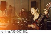 Купить «excited girl rock singer with guitar during rehearsal», фото № 33067882, снято 26 октября 2018 г. (c) Яков Филимонов / Фотобанк Лори