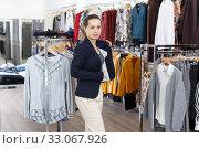 Купить «Woman trying blouse clothing boutique», фото № 33067926, снято 10 октября 2018 г. (c) Яков Филимонов / Фотобанк Лори