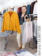 Купить «Woman holding lot of hanger with clothes», фото № 33067930, снято 10 октября 2018 г. (c) Яков Филимонов / Фотобанк Лори