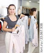 Купить «Woman demonstrating blouse on hanger», фото № 33067938, снято 10 октября 2018 г. (c) Яков Филимонов / Фотобанк Лори