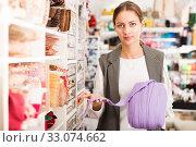 Купить «Female seller showing ribbons», фото № 33074662, снято 18 октября 2019 г. (c) Яков Филимонов / Фотобанк Лори