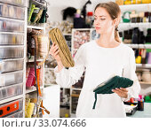 Купить «Interested young woman choosing colorful ribbons and braid for dressmaking in sewing supplies shop», фото № 33074666, снято 18 октября 2019 г. (c) Яков Филимонов / Фотобанк Лори